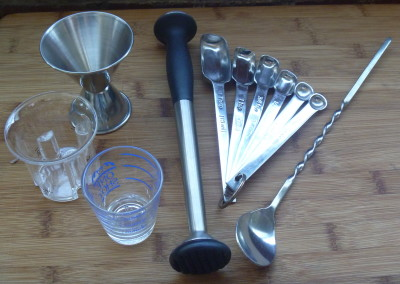 Measures and friends from l-r:  a trio of cocktail jiggers; a muddler; graduated measuring spoons; and a bar spoon.